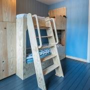 houten stapelbed met ladder in blauwe kamer
