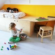 Houten bed met spelend meisje