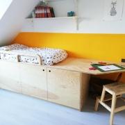 Houten bed onder schuin dak